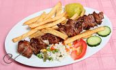 A lamb souvlaki or kebab on the skewer served with french fried potato chips rice and vegetables at a taverna. poster