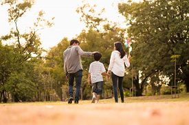 Scene From Behind Of Asian Happy Family Spend Time Together Walking And Relaxing At The Park In The