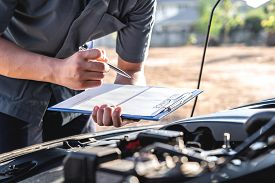 Technician Engineer Working Of Car Mechanic In Doing Checklist For Repairs Engine Writing To The Cli