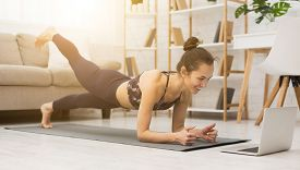 Girl Training At Home, Doing Plank And Watching Videos On Laptop, Training In Living Room