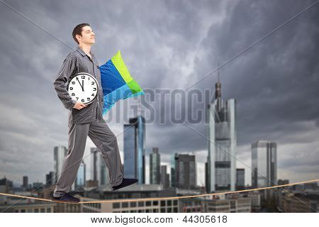 A man in pajamas holding a pillow and clock sleepwalking on a rope, with the financial centre in Frankfurt, Germany in the background