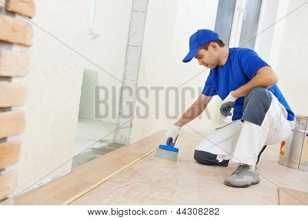 Handyman parquet carpenter worker adding glue on base during indoor wood flooring