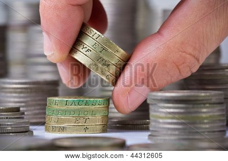 Closeup Of A Hand Withdraws British Pound Coins From The Stack