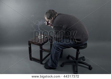 Deprimida joven sentado en una silla, fumando un cigarrillo