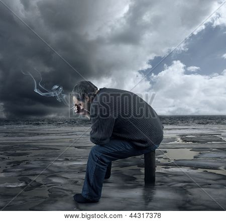 Depressed Young Man Sitting On A Chair, Smoking A Cigarette