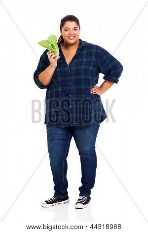full length of overweight young woman holding lettuce on white background