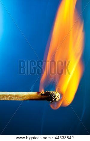 Burning match macro. On blue background.