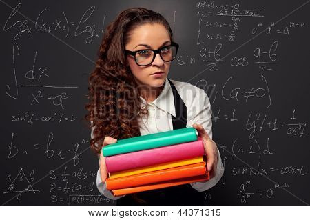 young teacher in glasses offering books over chalkboard