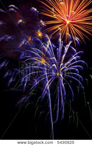 July 4th 2009 fireworks display in Pensacola Florida USA. Vertical dark night sky illuminated by white purple and orange explosions. poster