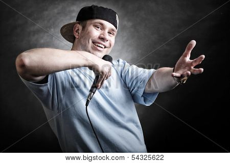 Rapper attitude rap singer hip Hop Dancer performing. Young man with microphone singing hand cool gesture black grunge background poster