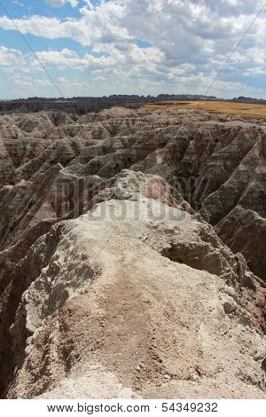 A serpentine trail to the edge of a cliff in the Badlands United States of America National Park in South Dakota scenic overlook on a beautiful summer day with fluffy cumulous clouds. poster
