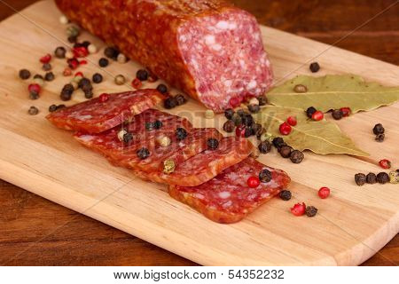 Tasty sausage on chopping board on browm background poster