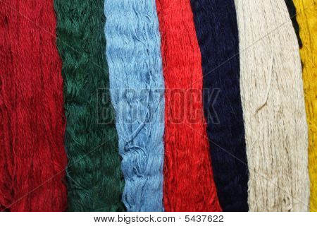 Bunch of colourful wool threads for handmade carpet poster