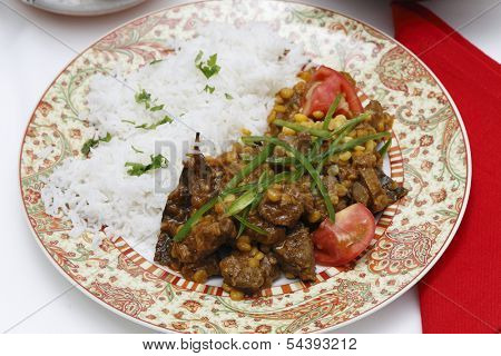 Lahore (Pakistan) style lamb and Chana dhal (split pea) curry, garnished with sliced chillies and chopped tomato, and served with white rice. poster