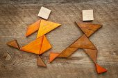 a couple of runners or athletes - abstract figures  built from tangram wooden pieces, a traditional Chinese puzzle game, artwork created by the photographer poster