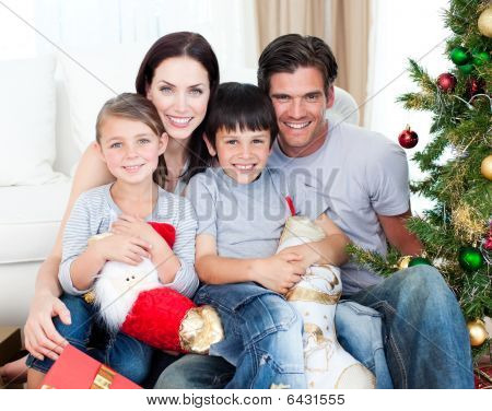 Portrait Of A Smiling Family At Christmas Time Holding Lots Of Presents