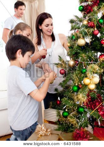 Happy Children And Parents Decorating A Christmas Tree