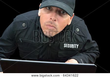 Security Working On Laptop, Looking To Camera