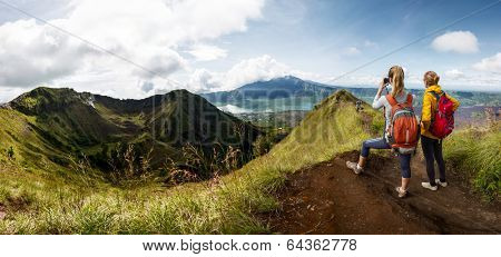 Two hikers with backpacks standing on top of the mountain enjoying valley view and taking a pictures with camera
