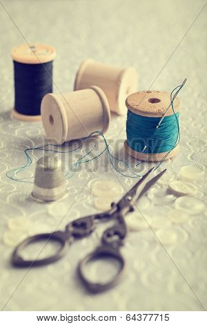 Threaded needle in cotton reel with sewing items - focus on threaded needle