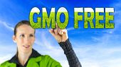 GMO Free conceptual image with a girl reaching up to touch text - GMO Free - in letters of green grass against a blue sky depicting cultivating healthy farm crops that are free of genetic modification poster