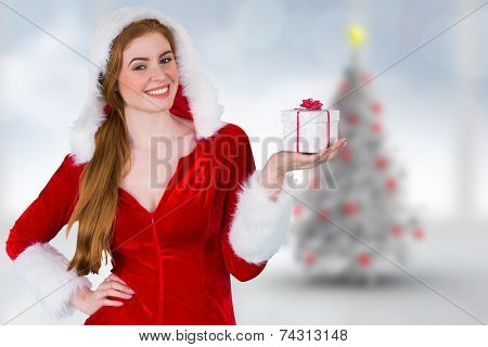 Pretty girl in santa costume holding gift box against blurry christmas tree in room poster