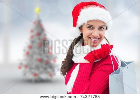 Festive brunette holding shopping bag against blurry christmas tree in room poster