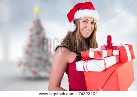 Festive blonde holding pile of gifts against blurry christmas tree in room poster