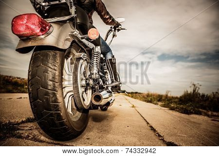 Biker girl riding on a motorcycle. Bottom view of the legs in leather boots. Focus on the rear wheel.