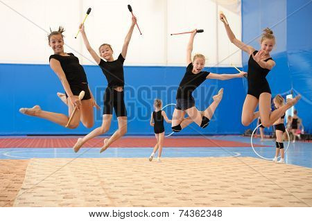 Girls with Indian clubs during high jump