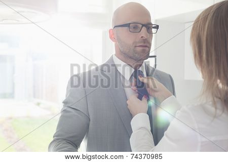 Woman adjusting businessman's tie at home