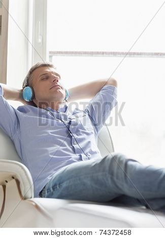 Relaxed Middle-aged man listening to music at home
