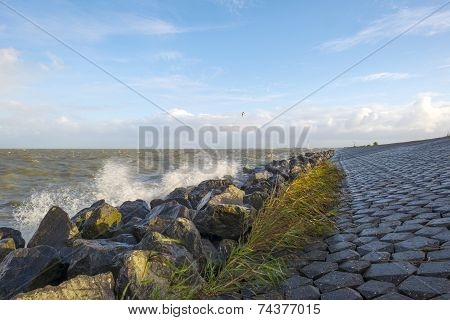 Basalt stones along a dike in a stormy sea poster