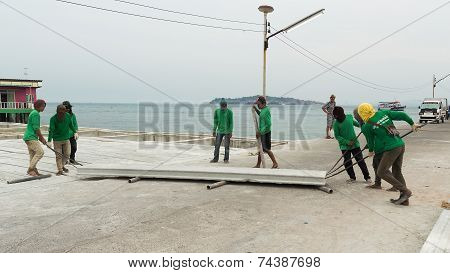 Pattaya, Thailand - January 14, 2012: Builders in Thailand roll a concrete plate in the afternoon