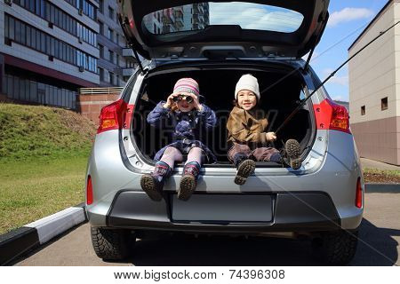 Children sitting in open trunk of car: boy with fishing rod, girl looking through binoculars