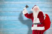 Santa claus ringing bell against blurred wooden planks poster