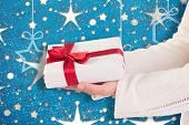 Woman offering a gift box against snowflake wallpaper pattern poster