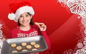 Festive little girl offering cookies against christmas themed snow flake frame poster