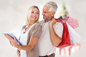 Happy couple with shopping bags and tablet pc against blurry christmas tree in room poster