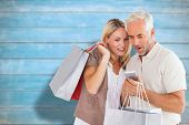 Happy couple with shopping bags and smartphone against blurred wooden planks poster