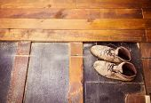 Old worker boots left on unfinished patio wooden flooring poster