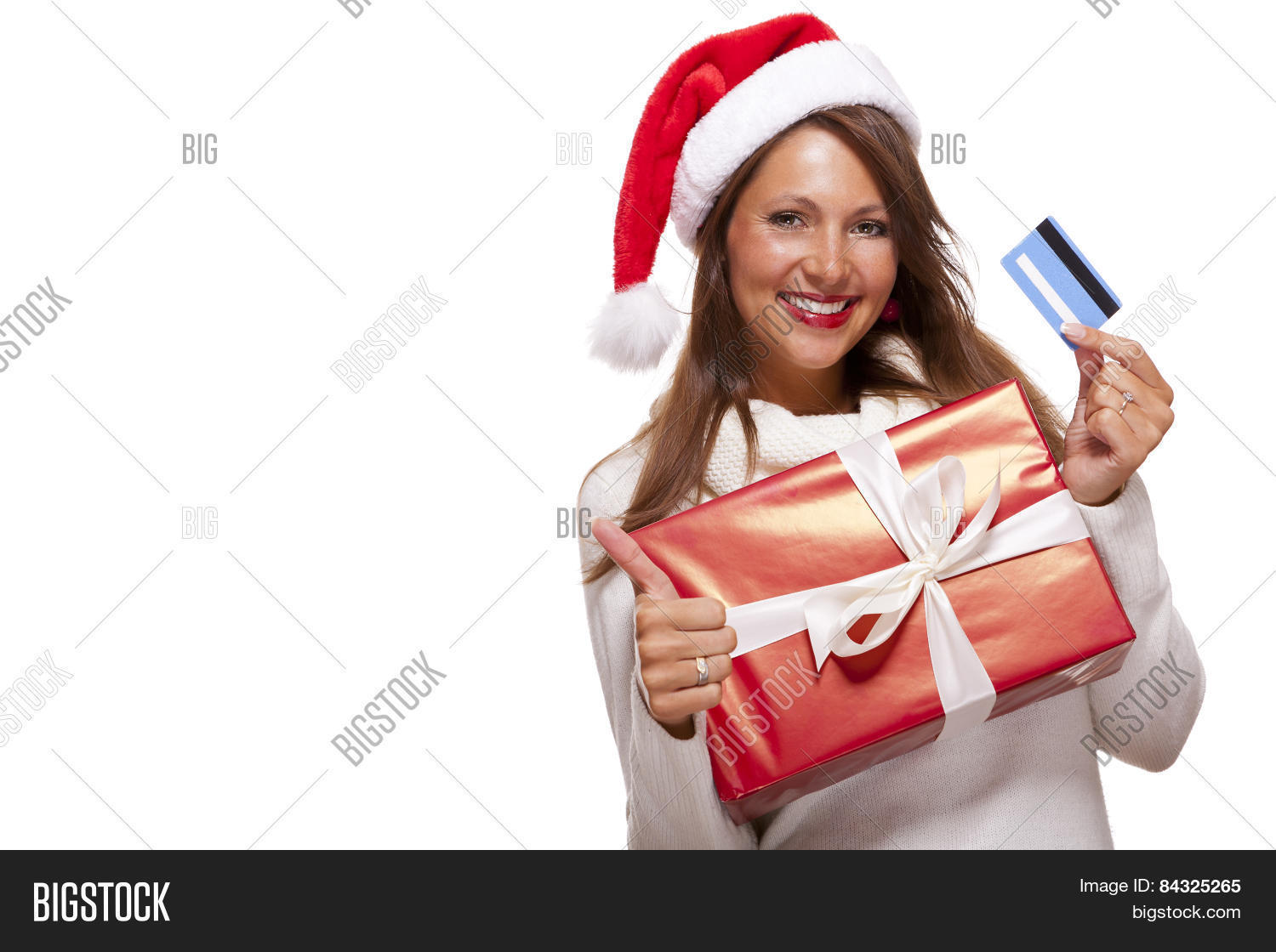 8f65ebd324a26 Smiling woman wearing a red Santa hat purchasing Christmas gifts on a bank  card holding up a colorful red giftwrapped box with a happy smile and a thumbs  up ...