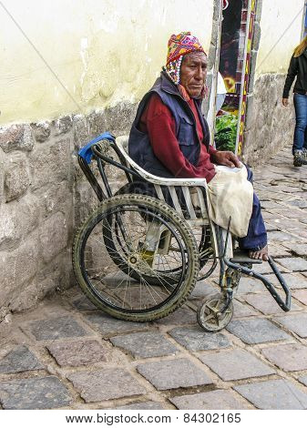 Handicapped Man Sits In An Wheelchair And Begs For An Alm