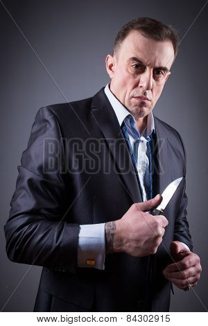 adult male gangster in a business suit with a knife poster