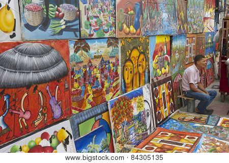 Man sells works of local artists at the street in Santo Domingo, Dominican Republic.