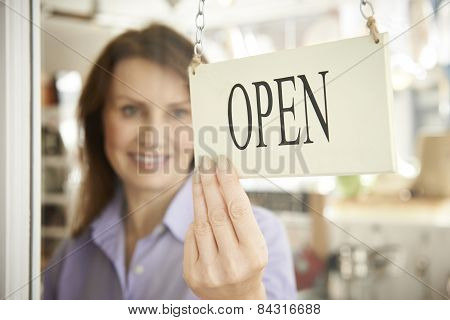 Store Owner Turning Open Sign In Shop Doorway poster