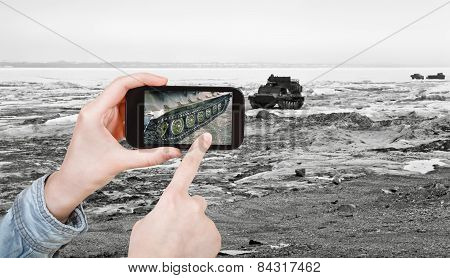 travel concept - tourist taking photo of tracked vehicle on ice road on mobile gadget Anadyr Chukotka Russia poster