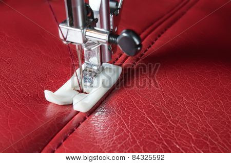 sewing machine and red leather with a seam close-up poster