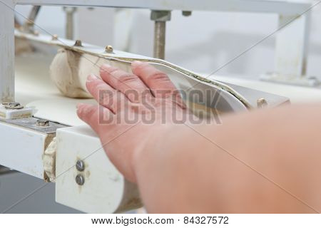 Dough divider and moulder machine at work. Manufacturing process of spanish bread poster