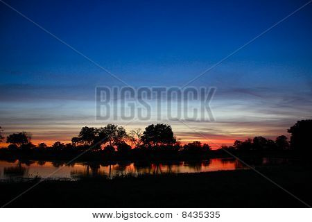 Blue And Red Sunset Over River With Hippos